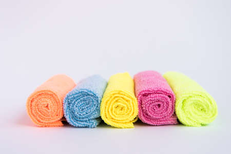 Multicolored microfiber cloths, folded into rollers. The fabrics are laid out in a row. Towels. Фото со стока