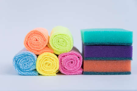 Multi-colored foam sponges for washing dishes and microfiber cloths. All multicolored items on a white background.