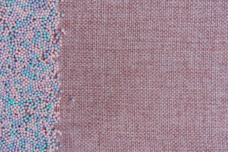 Background of linen yarn, burlap. On one side, the card is decorated with pastry topping. All in pink and blue shades. Sweet background.