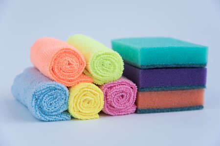 Multi-colored foam sponges for washing dishes and microfiber cloths. All multicolored items on a white background. Items for home cleaning.