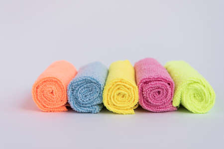 Multicolored microfiber cloths, folded into rollers. The fabrics are laid out in a row. Towels. 版權商用圖片