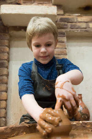 A child learns to make pottery on a Potters wheel. Leisure home.