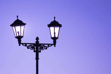 Urban landscape. Street lamp with a lamp in a classic style against a purple sky. Beautiful postcard.