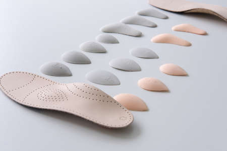 The process of manufacturing individual orthopedic insoles for people with foot diseases, flat feet. Close-up of the insole and accessories for it.
