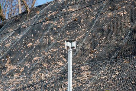 Strengthening the mountain slope with a metal mesh that prevents rockfall on the road. Abstract background of the security concept. 版權商用圖片