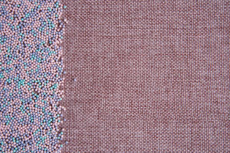 Background of linen yarn, burlap. On one side, the card is decorated with pastry topping. All in pink and blue shades. Sweet