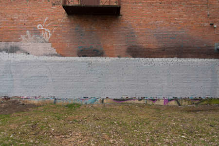 Graffiti-covered pavement against a brick wall. The concept of prohibition.