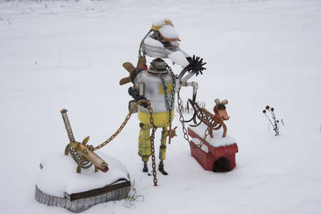 Sculpture of a little man made from parts of old cars. The hero has two dachshunds on a leash. Dogs are also made from car parts. Handmade work.
