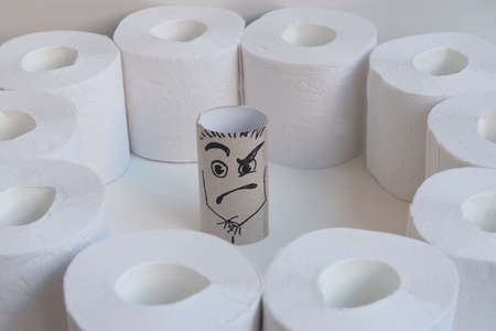 The empty sleeve of toilet paper. The sleeve is surrounded by toilet paper rolls. A grimace of anger and horror is drawn. The concept of exposure. Stok Fotoğraf - 146961956