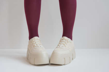 long slender legs close-up. Thick-soled sneakers. Red stockings or tights. Trend, fashion