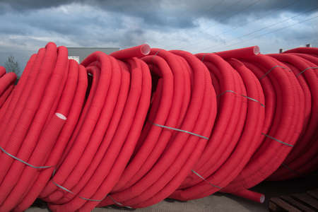 Red plastic pipes rolled into open air rolls. Construction