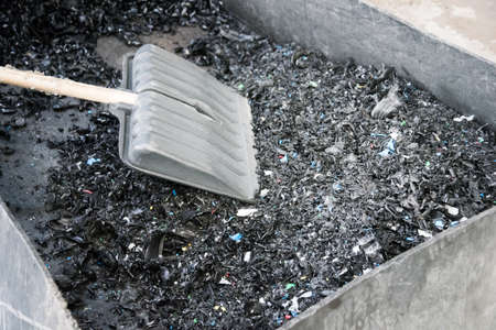 Container with crushed plastic at the factory. Shovel. Particles of crushed plastic are black in color. Reuse. The concept of caring for the environment.