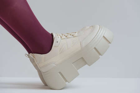 legs below the knee close-up. Shoes with a solid sole. Red stockings or tights. Trend, fashion