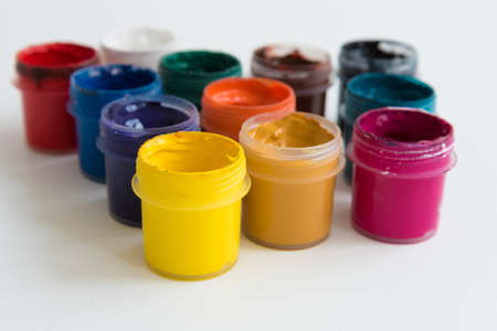 Open cans of paint, top view. Variety, many colors of gouache. texture. Imagens