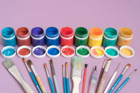 Jars with gouache and brushes for drawing different shapes and sizes. Variety of color. The concept of diversity and choice in creativity. Pink Imagens