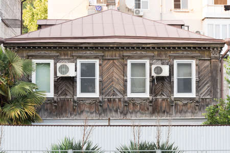 Very old wooden house with modern Windows and air conditioning. Eclecticism. Concept.