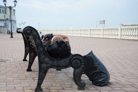 A man sleeps on a street bench. The seafront promenade. Concept of relaxation and recreation.