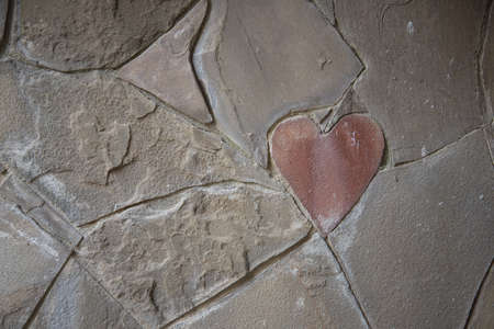 Stone wall cladding. Among the usual forms, there is a heart-shaped stone. Declaration of love. A symbol, a sign of love.