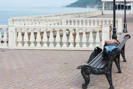 A man sleeps on a street bench. The seafront promenade. Concept of relaxation Foto de archivo
