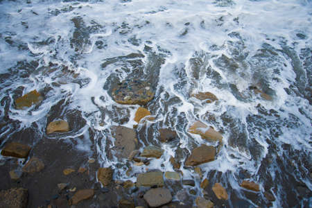 Top view of the sea wave and rocks. The water forms a whimsical pattern. Background