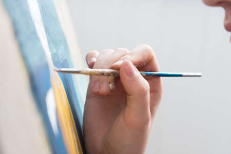 The artist is painting a picture. Canvas and brush in hand close-up. work Archivio Fotografico