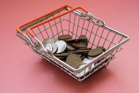 There is a handful of coins in the shopping basket. The concept of buying or selling currency. Purchases and expenses. Russian