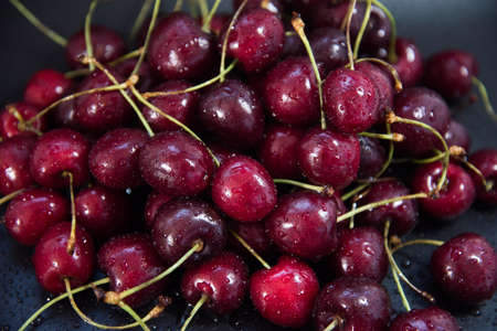Red fresh cherries on a black background. Drop of water. The concept of freshness. 版權商用圖片