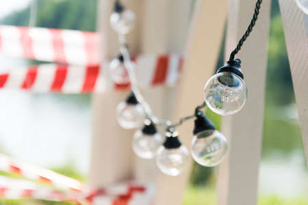 Holiday lights on a background of red tape prohibiting. The concept of banning parties during the epidemic. Stock Photo