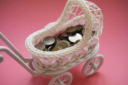 There are coins in the pram. Close up. Concept of state support. Concept of child trafficking. Maternity capital.