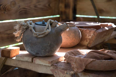a crude earthenware teapot stands on a wooden shelf in the pottery shop. Eco-friendly dishes. Handmade work.