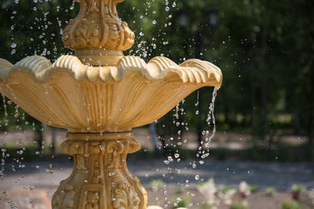 Fountain element close-up. The concept of summer freshness and vacation. Flying drops of water.