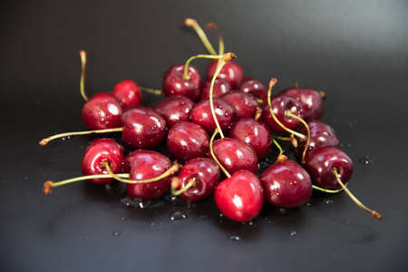 Red fresh cherries on a black background. Drop of water. Close up. The concept of freshness.
