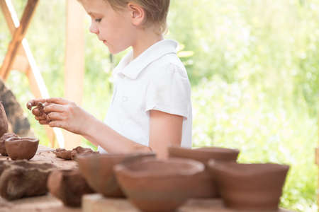 The child makes dishes and various figures from clay. Pottery skills. Hobbies and interests. Childrens education, expanding horizons.