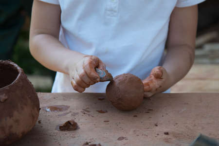 Close-up of childrens hands working with clay. The child makes dishes and other crafts. Pottery. Concept of Hobbies and Hobbies, comprehensive development of the child.