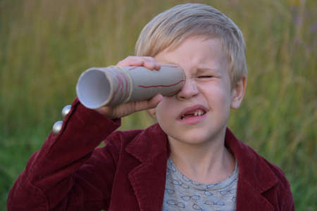 the child looks into a homemade telescope