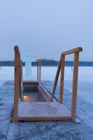 A hole for bathing on the feast of Epiphany. Outdoor plunge pool, the lake. A cross made of ice