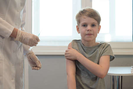 The child smiles after the injection, after the vaccination. The doctor is standing nearby, the syringe is visible. The child looks calmly at the camera and smiles Stock fotó