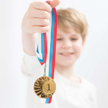 A happy child holds a medal in his hand in front of him. Gold medal. Achievements in sports. Academic achievement. A wide and happy loss in a blond child Stok Fotoğraf