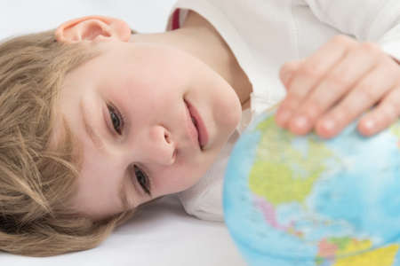 The child dreamily examines the globe. Travel yearning concept. Closed borders and quarantine. A European-looking child dreams of travel