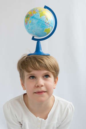 The child is holding a globe on his head in balance. The concept of the dependence of the earth on the future generation