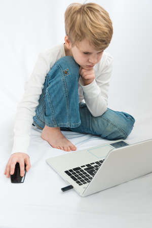A child of the European type is sitting barefoot in front of a laptop. The blond looks attentively at the monitor. Cozy home environment. Home schooling concept. Enthusiastic computer game