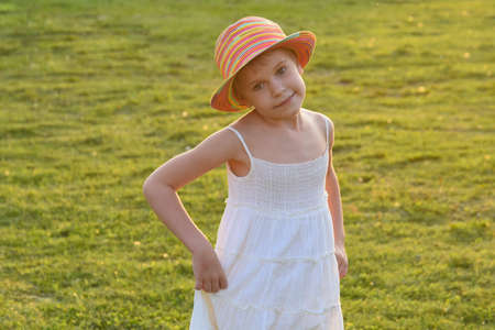 little girl dances and whirls in the sun. Carelessness and happiness