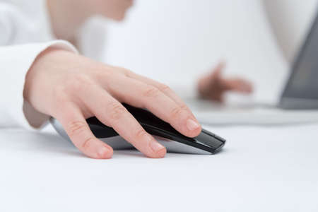 Childrens hand close up. The child is engaged or plays in the laptop using a wireless mouse
