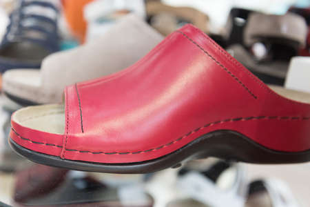 The shop window displays comfortable orthopedic shoes. Modern style red leather shoes. Taking care of your feet. Prevention and treatment of flat feet Stok Fotoğraf