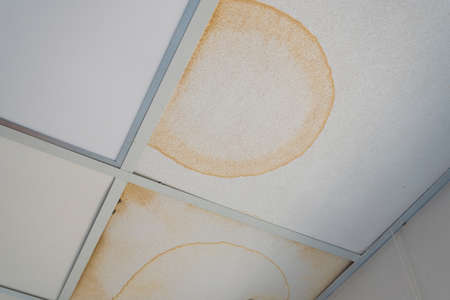 False ceiling leaks. Yellow dirty stains from the pipe break. Emergency situation, destruction of the roof Stok Fotoğraf