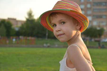 Portrait of a beautiful girl in a summer dress and a colorful hat. The girl looks into the camera. A child in the rays of the setting sun