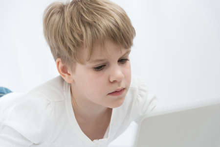 The blond child looks attentively at the computer or laptop screen. Close-up portrait Stok Fotoğraf