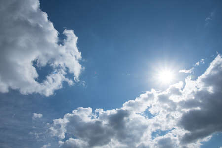 Blue sky, white clouds and sun. Background, texture.