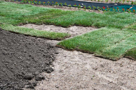 Rolls of green lawn prepared for planting. A pile of fertile soil. Landscaping design, arrangement of the territory