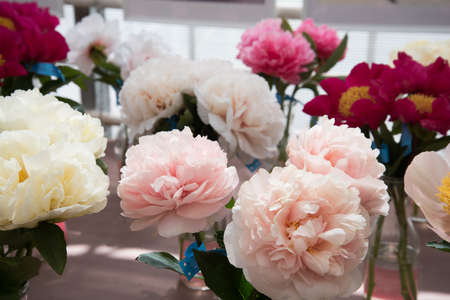 Floral exhibition. Peonies of different colors are in transparent vases. Various varieties of beautiful flowers.